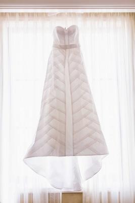 Anne Barge strapless wedding dress hanging in sunlit bridal suite room