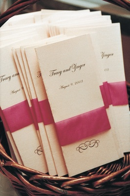 Ceremony programs tied with pink ribbon in basket