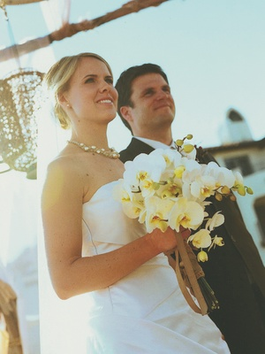 Bride holding flowers wearing short necklace