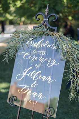 Jillian Murray and Dean Geyer wedding ceremony welcome sign with fresh greenery gold calligraphy