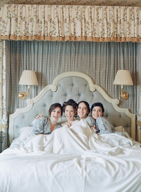 Bride in hair rollers with blue robes under sheet in bed