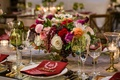 Low wedding centerpiece green glassware white red pink orange flowers monogram menu burgundy napkin