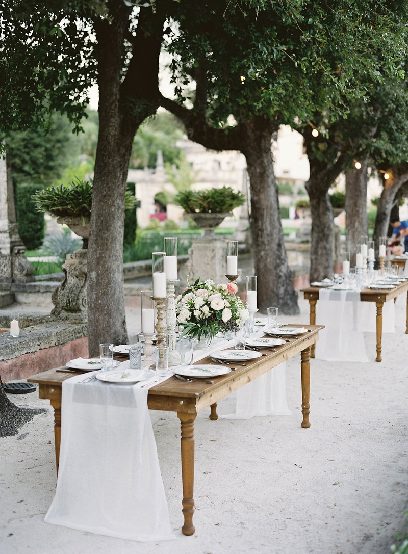 Wedding reception tables without chairs wood white linen runner candlesticks neutral flowers