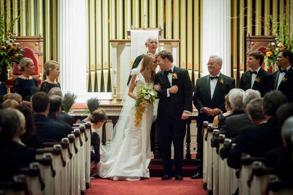 Bride and groom touch foreheads at traditional church wedding