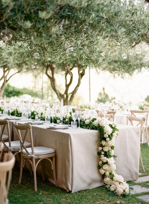 Wedding reception long reception table vineyard chairs greenery garland white flowers trees orbs