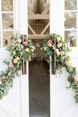 Large white barn farmhouse doors decorated with greenery pink rose yellow rose orange rose flowers