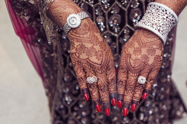 indian-american bride with elaborate henna tattoos on hands, diamond engagement ring and right hand