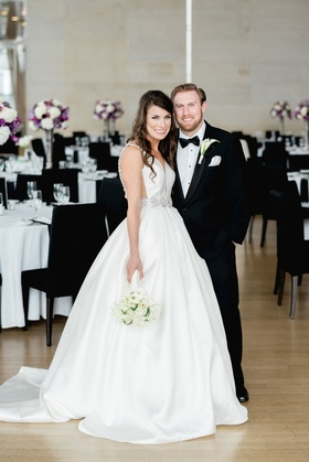 Wedding portrait in venue space ballroom wood floor black chairs purple white flowers wedding dress