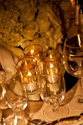 White votive candles in gilt pillar vases