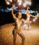destination wedding in mykonos greece fire dancers painted gold on beach entertainment performers