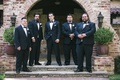 Groom and groomsmen in black tuxedos, white rose and white anemone boutonnieres at Hummingbird Nest