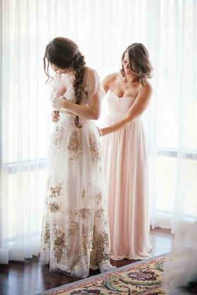 Bride in a Claire Pettibone dress with gold and silver embroidery, loose braid, and bridesmaid