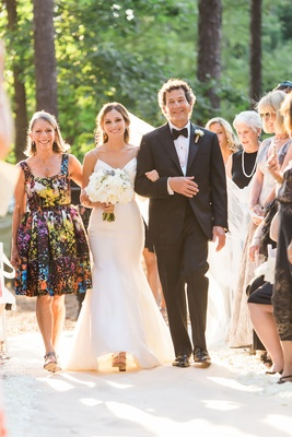 Bride walking down aisle with father in tuxedo and mother in short cocktail dress colorful design