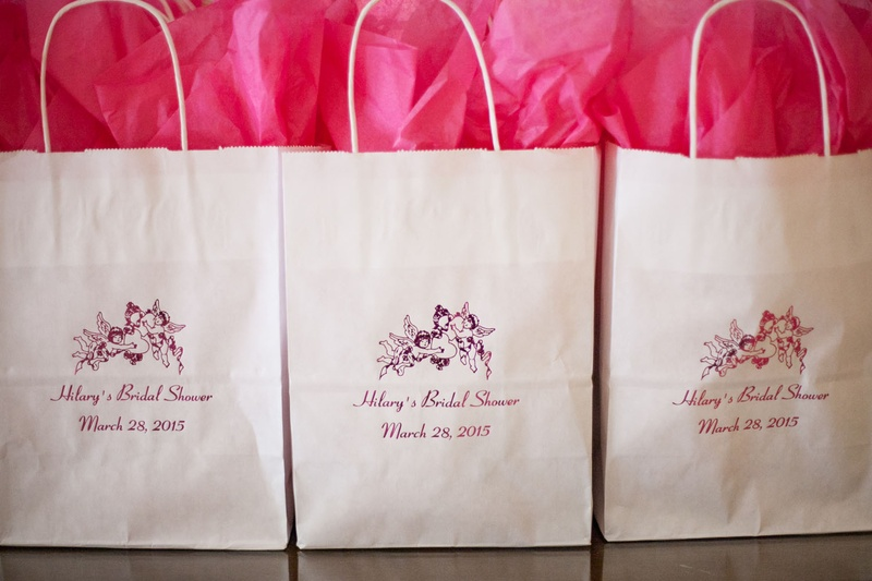 white gift bags with pink tissue paper for bridal shower goodie bags