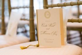 Wedding ceremony program white stationery gold lettering monogram tie tassel on chair