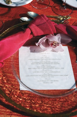 glass charger over red tablecloth with red napkin and pink flower