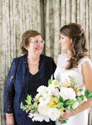 Mother of bride in string of pearls and navy blue ensemble lace v neck jacket bouquet white yellow