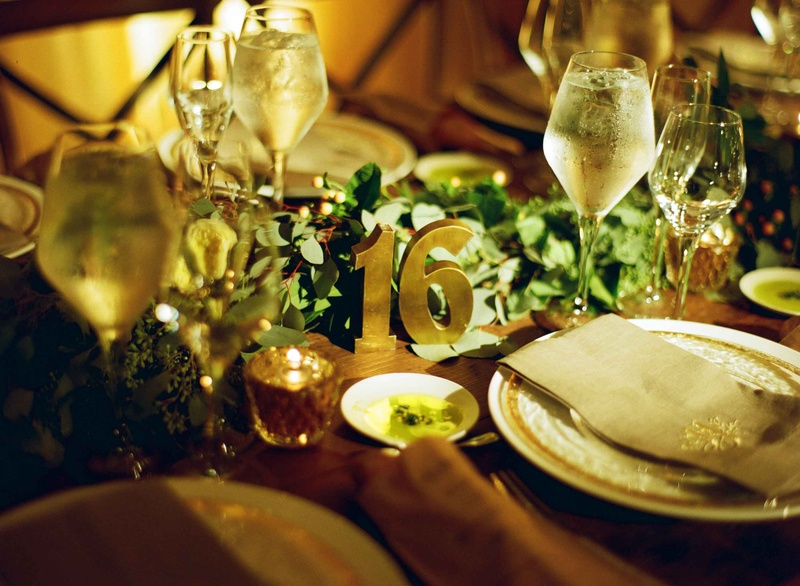 Wood table with eucalyptus leaf greenery runner and brass table number 16 sculpture