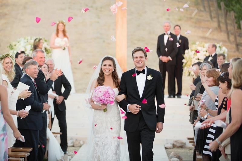 Wedding guests toss pink petals on newlyweds