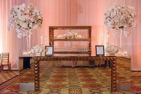 Ballroom wedding reception mirror bar with pyramid studs gold two large flower arrangements roses