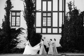 black and white photo of bride in a line gown veil being held by bridesmaids maid of honor outside
