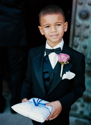 African American ring bearer in tux holding blue ring pillow
