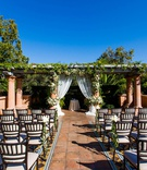 wedding ceremony outdoors tile floor trellis greenery white chuppah