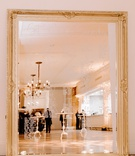 gold framed mirror seating chart, pillar candles, rose petals on floor