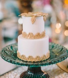 two tier small white wedding cake gold accents blue stand