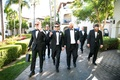 Groom and groomsmen walking through venue bow ties suits tuxedos dress shoes black sunglasses