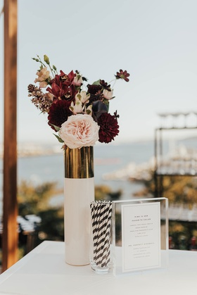 outdoor cocktail hour pink and burgundy rose flowers dahlia white gold vase black white stripe straw