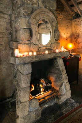 Wedding reception in adobe room with a stone fireplace, mirror, candles at San Ysidro Ranch