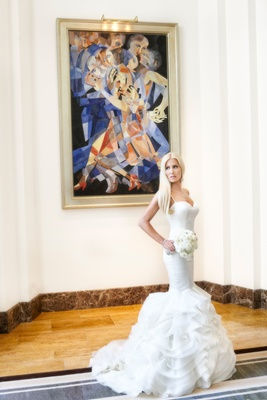 bride in rivini ruffled mermaid wedding dress in front of abstract painting