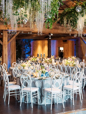 curved x-back white chairs, silver-blue linens with doily pattern