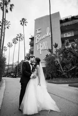 Black and white photo of bride in Monique Lhuillier and groom in front of The Beverly Hills Hotel