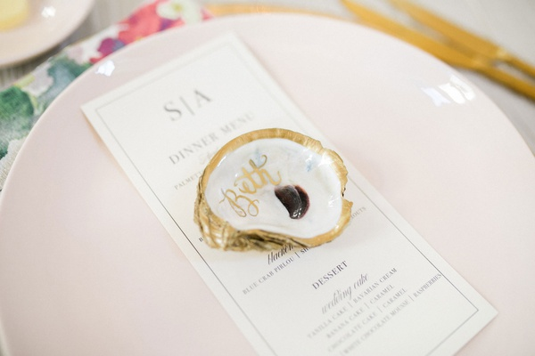 wedding guest place setting light pink plate with gold rim and calligraphy oyster shell place card