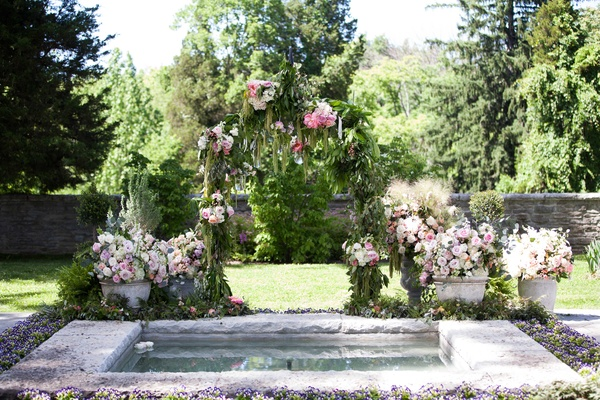 a custom secret garden inspired arch with dripping greenery and pink and purple flowers