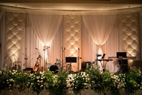 live band stage greenery along edge with drapes curtains and tufted panel wall behind performers