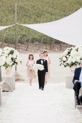 Ring bearer holding pillow down vineyard wedding aisle