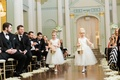 Two flower girls walk down the aisle toss flower petals as guests look on wood floor Biltmore
