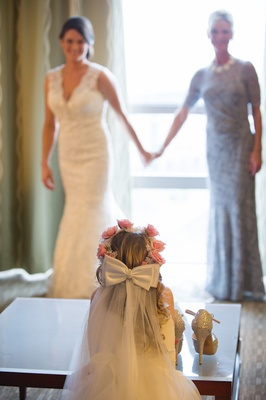 Flower girl watching bride get ready in suite