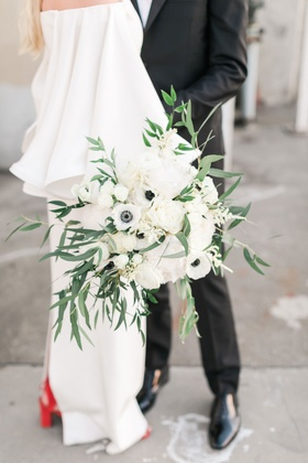 Greenery overflowing from ivory bridal bouquet