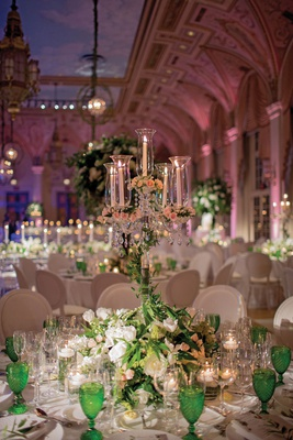 candelabra with tapered candles, candelabra wrapped in greenery, blush blossoms