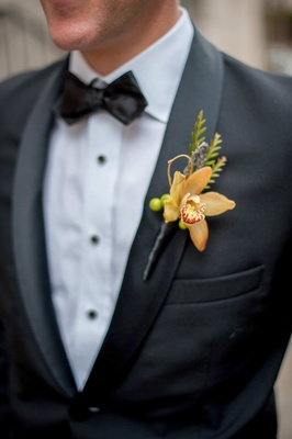 Groom in tuxedo with orange orchid boutonniere