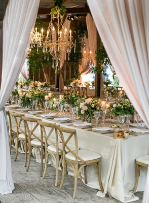 Long reception table wedding wood chairs low centerpieces greenery chandelier drapes