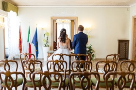 Bride and groom facing officiant wedding ceremony in Venice Italy at palazzo palace flags minimal