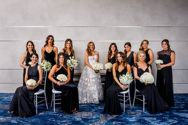 bride in reem acra wedding dress from dimitra's bridal couture bridesmaids in designer black dresses