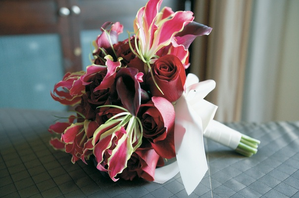 Red and pink wedding bouquet with rose, lily, and calla lily flowers