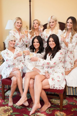bride and bridesmaids in floral robes with champagne