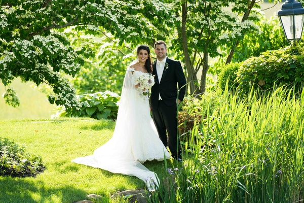 Bride and groom in grass field next to pond